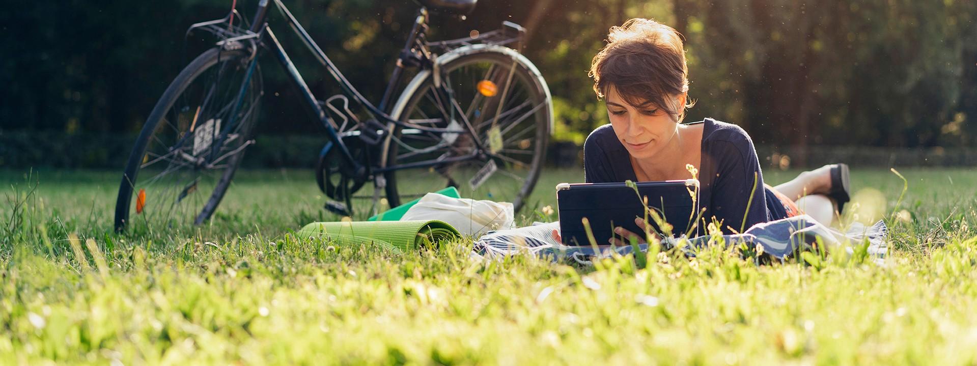 Frau liegt neben ihrem Fahrrad auf einer Sommerwiese