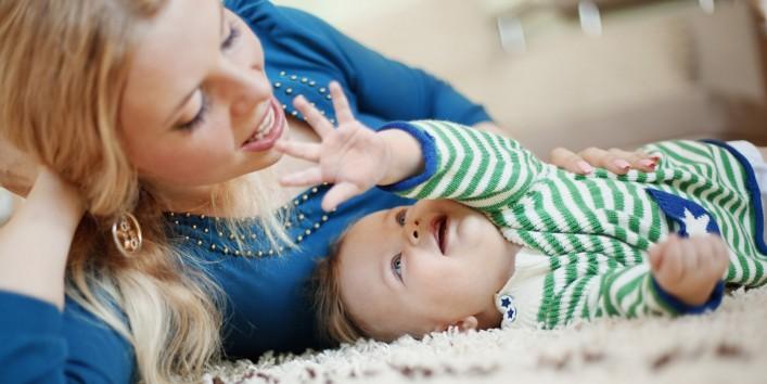 Eine etwa 30-jährige Mutter und ihr Säugling liegen auf einem Teppich und spielen miteinander.