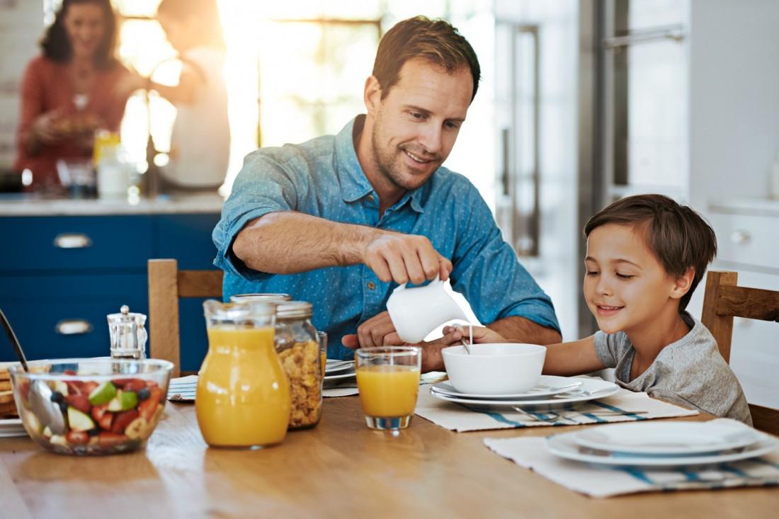 Vater gießt Sohn Milch ins Müsli am Frühstückstisch