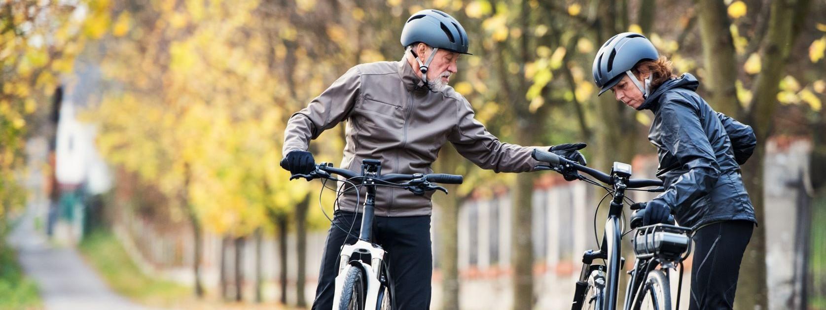 Ein etwa 60 jähriges Pärchen steht an einer asphaltierten Straße und prüft ihre Fahrräder.