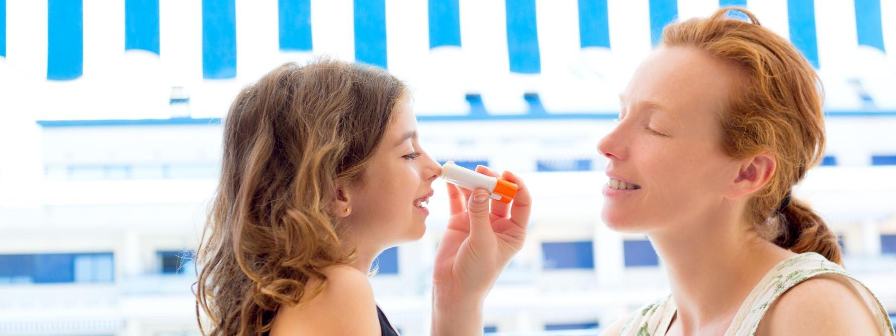 Eine etwa 35 jährige Frau trägt ihrer etwa 6 jährigen Tochter Sonnenschutz im Gesicht auf.
