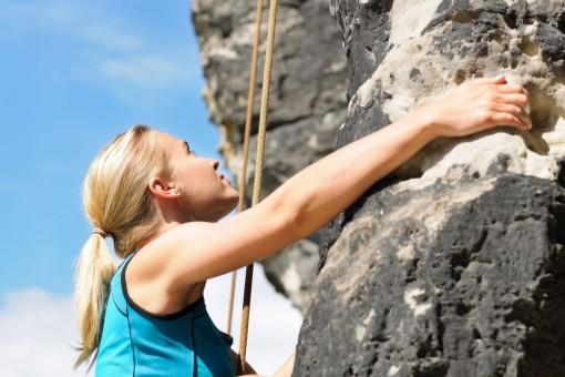 Eine etwa 30 jährige Frau klettert eine Felswand empor. Dabei schaut sie konzentriert nach oben.