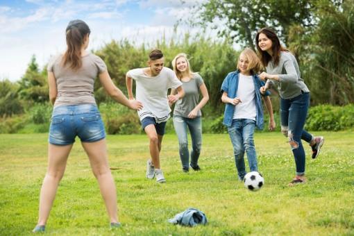 Eine Gruppe von Teenagern spielt in einem Garten auf einem rasen gemeinsam Fußball. Alle lachen ausgiebig.