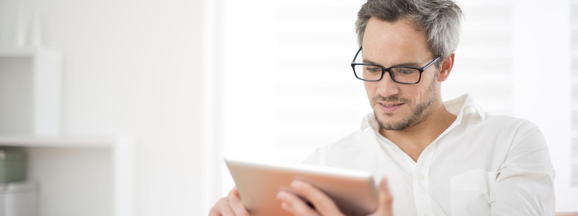 Ein etwa 45 jähriger Mann sitzt auf einem Sofa und schaut auf ein Tablet.