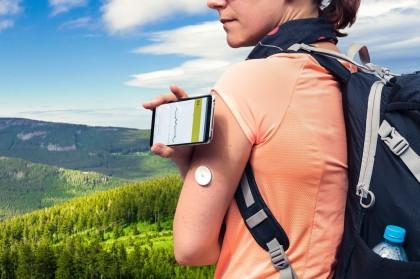 Frau mit Rucksack steht in den Bergen und misst mit einem Sensor und einem digitalen Lesegerät ihren Blutzucker
