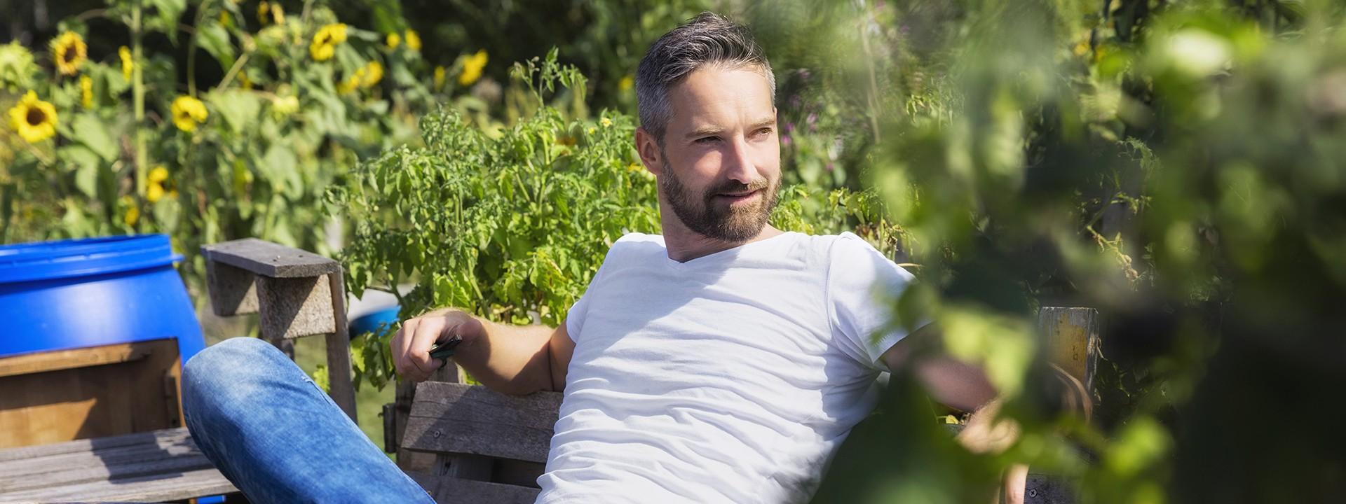 Mann sitzt entspannt auf einer Bank im Grünen