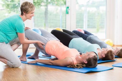 Eine Frauensportgruppe machen Übungen für den Beckenboden auf ihren Sportmatten. Eine Trainerin hilft einer Teilnehmerin und stützt ihr Becken.