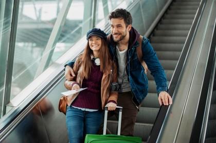 Frau und Mann lächeln auf einer Rolltreppe.