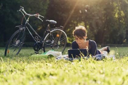 Frau neben Fahrrad auf Wiese mit Tablet