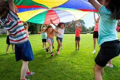 Kindergruppe spielt mit einem bunten Fallschirmtuch.