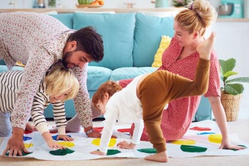 """Eine junge Familie spielt mit ihren zwei Jungs am Boden das Spiel """"Twister"""". Alle haben Spaß und lachen ausgiebig."""