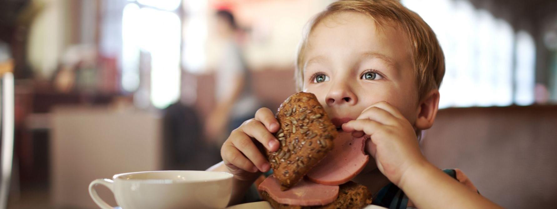 Ein etwa 3 jähriges Kind sitzt am Tisch und beißt von einem belegten Wurstbrötchen ab.