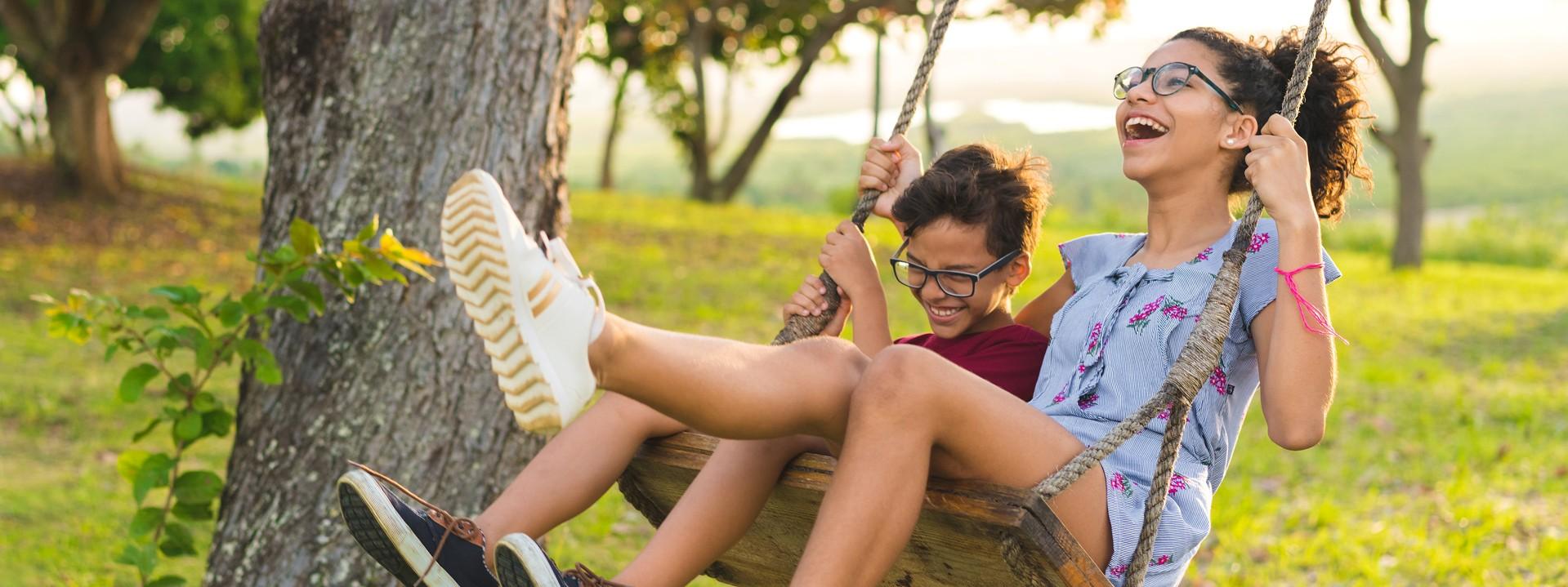 zwei Kinder auf einer Schaukel