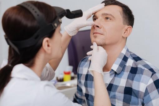 Ein etwa 35 jähriger Mann lässt sich von einer Ärztin an der Nase untersuchen.