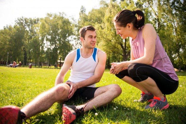 Ein Pärchen befindet sich auf einer Wiese im Park. Der Mann liegt auf dem Boden und umfasst seinen rechten Oberschenkel. Die Frau hockt daneben und spricht mit ihm