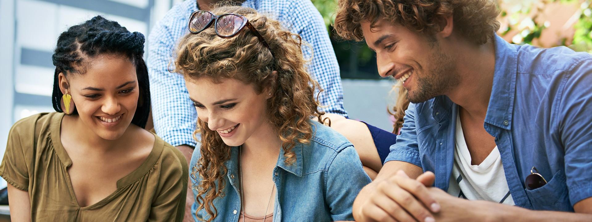 Studenten und Studentinnen sitzen nebeneinander auf einer Treppe und schauen auf einen Laptop.