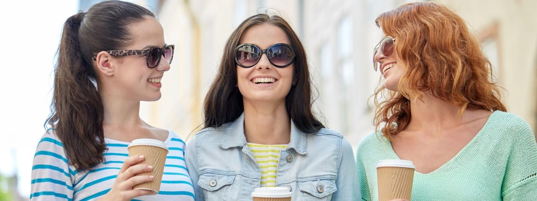 Drei junge Frauen laufen durch eine Stadt. Sie tragen Sonnenbrillen und trinken Kaffe-to-go. Alle lachen ausgiebig.