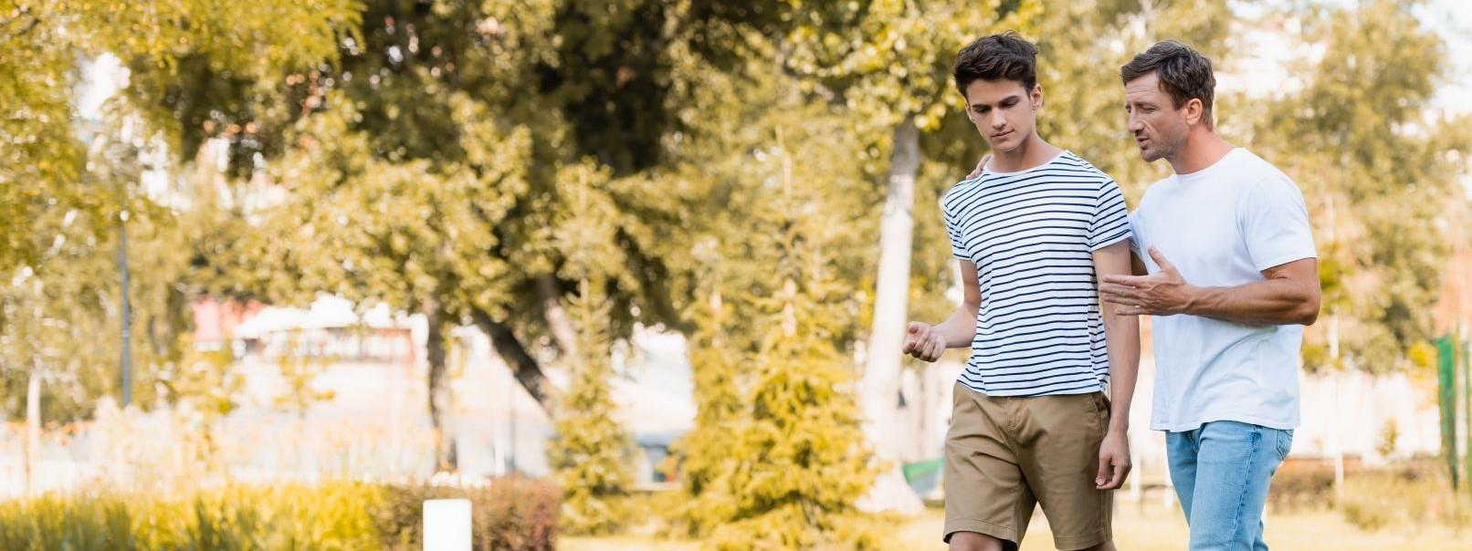 Ein Mann läuft mit seinem etwa 16 jährigen Sohn über eine Wiese. Beide unterhalten sich angeregt.