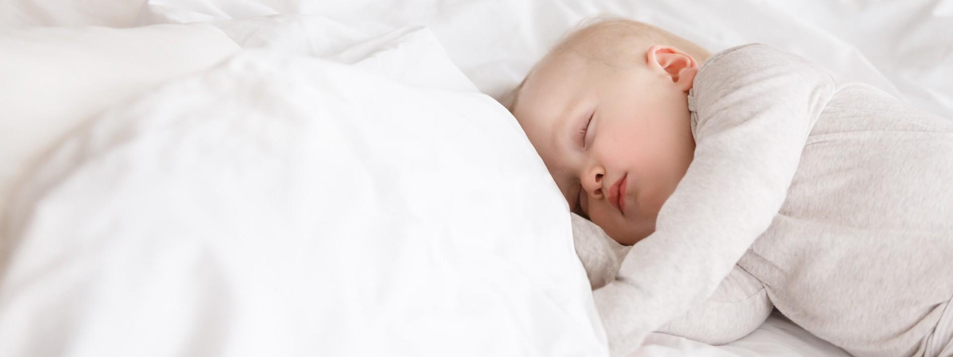 Kleinkind schläft im weißen Bett.