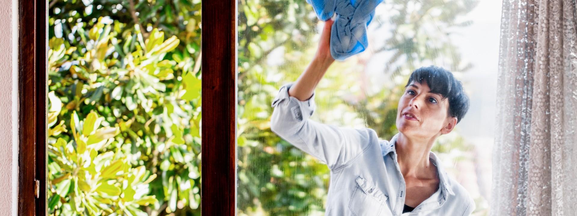 Dunkelhaarige Frau putzt ein Fenster.