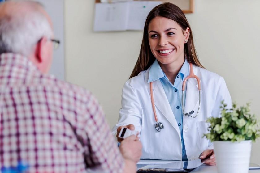 Eine Ärztin reicht einem Pateinten eine Versichertenkarte. Dabei lächelt sie.