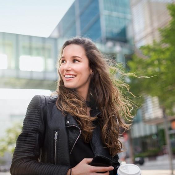 Ein circa 18-jährige Auszubildende ist an einem schönen Tag in der Stadt unterwegs. Sie genießt die Sonne. In ihren Händen hält sie ihr Smartphone und einen Coffee To Go Becher.