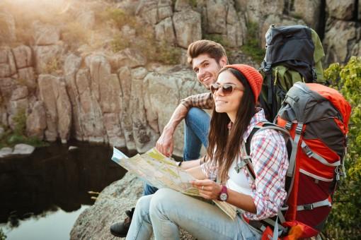 Ein etwa Mitte 20 jähriges Paar sitzt an einem Felsenrand und schaut in die Ferne. Beide haben Wanderrucksäcke auf. Die Frau hält eine Karte in den Händen.