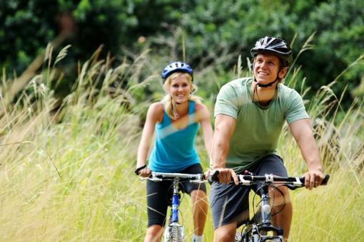 Ein etwa 35 jähriges Pärchen fährt mit den Fahrrädern durch die Natur.