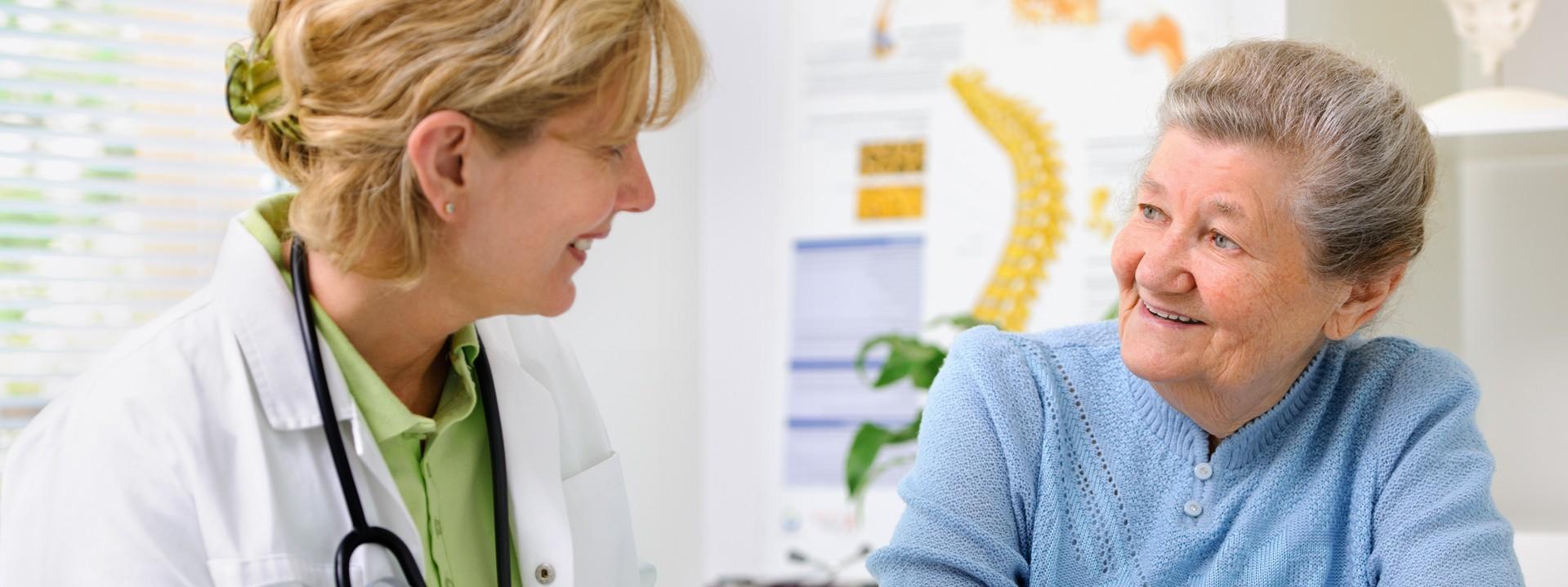 Eine Seniorin im blauen Pullover sitzt in einem Behandlungszimmer einer Ärztin gegenüber. Beide lächeln sich an.