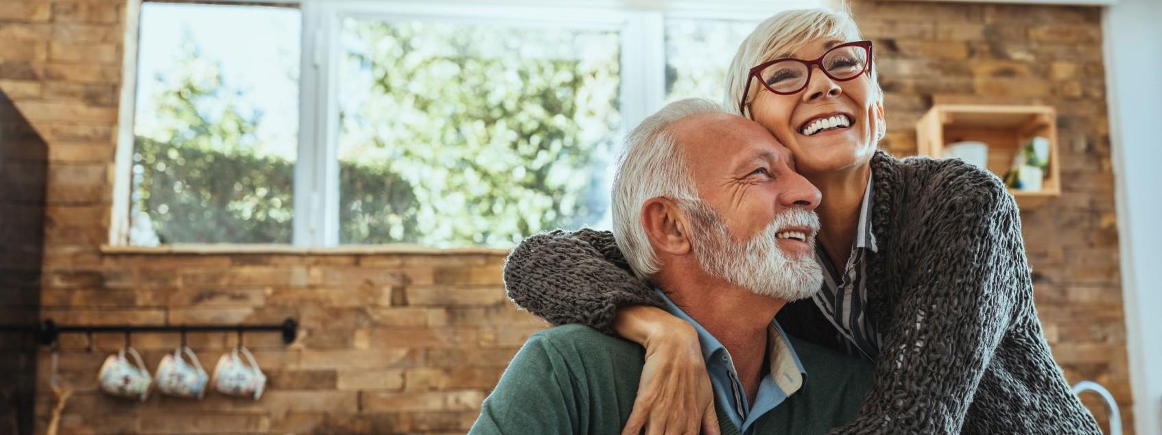 Ein Seniorenpaar sitzt an einem Tisch in der Küche. Die Frau umarmt ihren Mann von der Seite. Beide lachen ausgiebig.