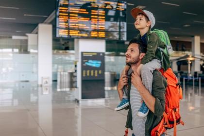 Vater mit Sohn auf den Schultern im Flughafen.