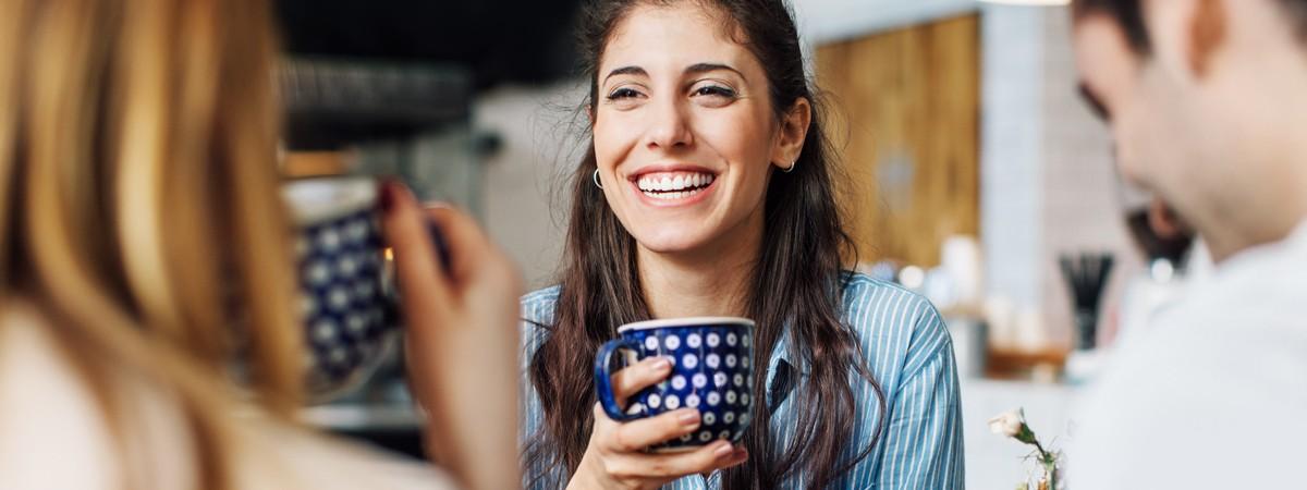 Eine 35-jährige Frau unterhält sich gut gelaunt bei einem Kaffee mit ihren Freunden.