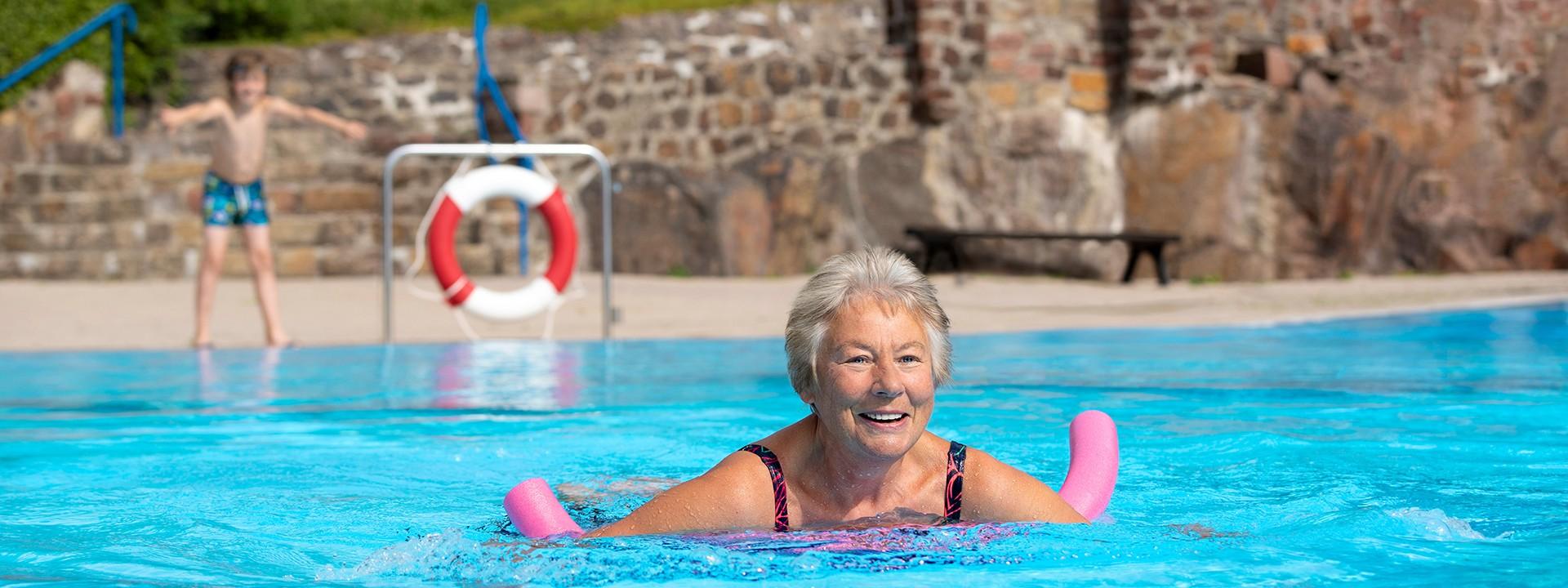 Oma schwimmt mit Schwimmnudel