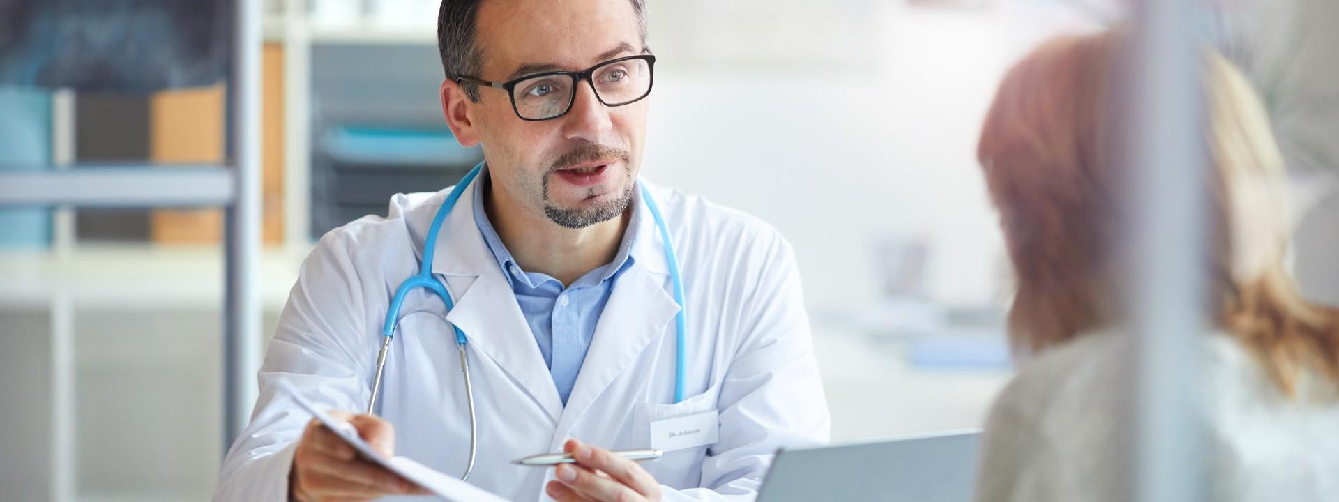 Ein etwa 45 jähriger Arzt berät eine Frau in einem Behandlungszimmer. Auf dem Tisch zwischen ihnen steht ein Laptop.
