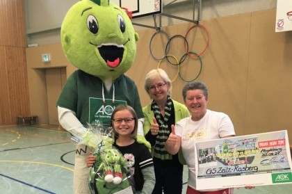 Das AOK-Maskottchen Jolinchen übergibt dem Schulkind Lia aus Zeitz einen Preis für ein Gewinnspiel. Auf dem Bild sind außerdem noch die Landesrepräsentantin der AOK und die Klassenlehrerin von Lia.