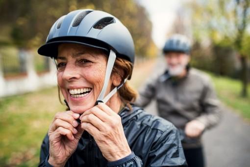 Eine etwa 60 jährige Frau fährt Fahrrad und trägt einen Helm. Dabei lächelt sie ausgiebig. Im Hintergrund befindet sich ihr Partner, der ebenfalls Fahrradfährt.