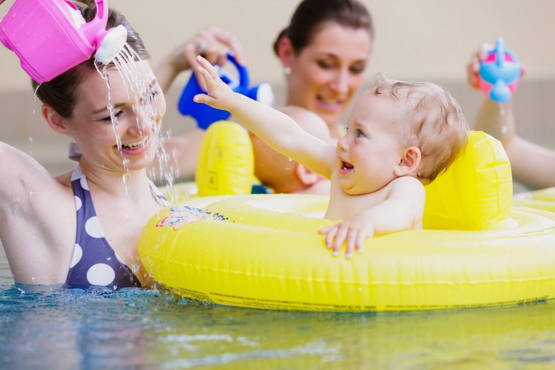 Mutter spielt mit Kind beim Babyschwimmen