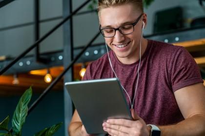 Junger Mann hat Tablet PC in der Hand und Kopfhörer im Ohr.