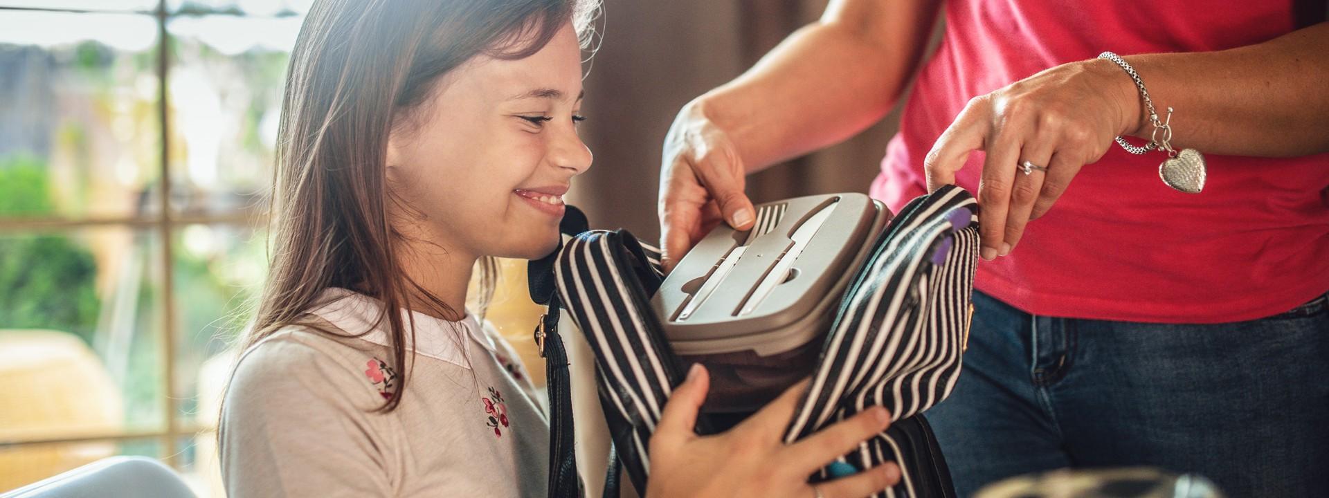 Mädchen bekommt Brotdose von Mutter