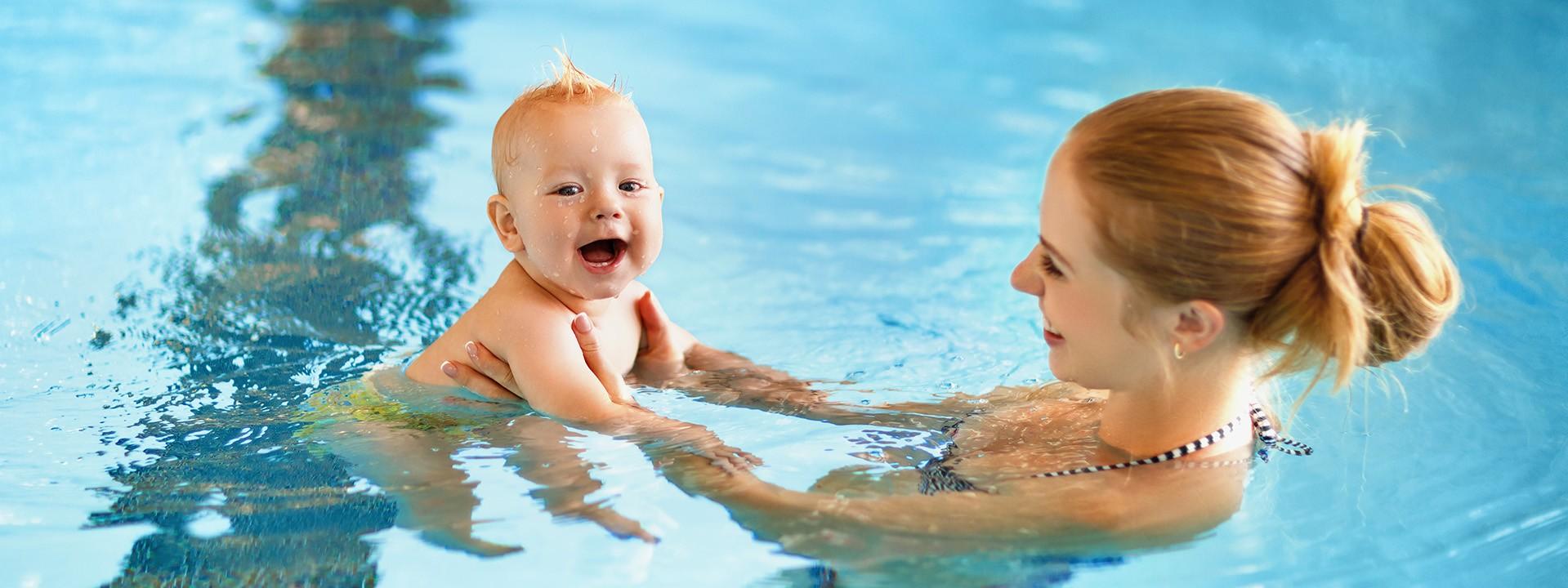 Mutter hält ihr Baby an den Händen und lässt es durch das Wasser gleiten
