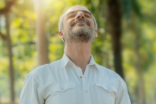 Ein etwa 45 jähriger Mann steht in der Natur und atmet tief ein. Er hat seine Augen geschlossen.