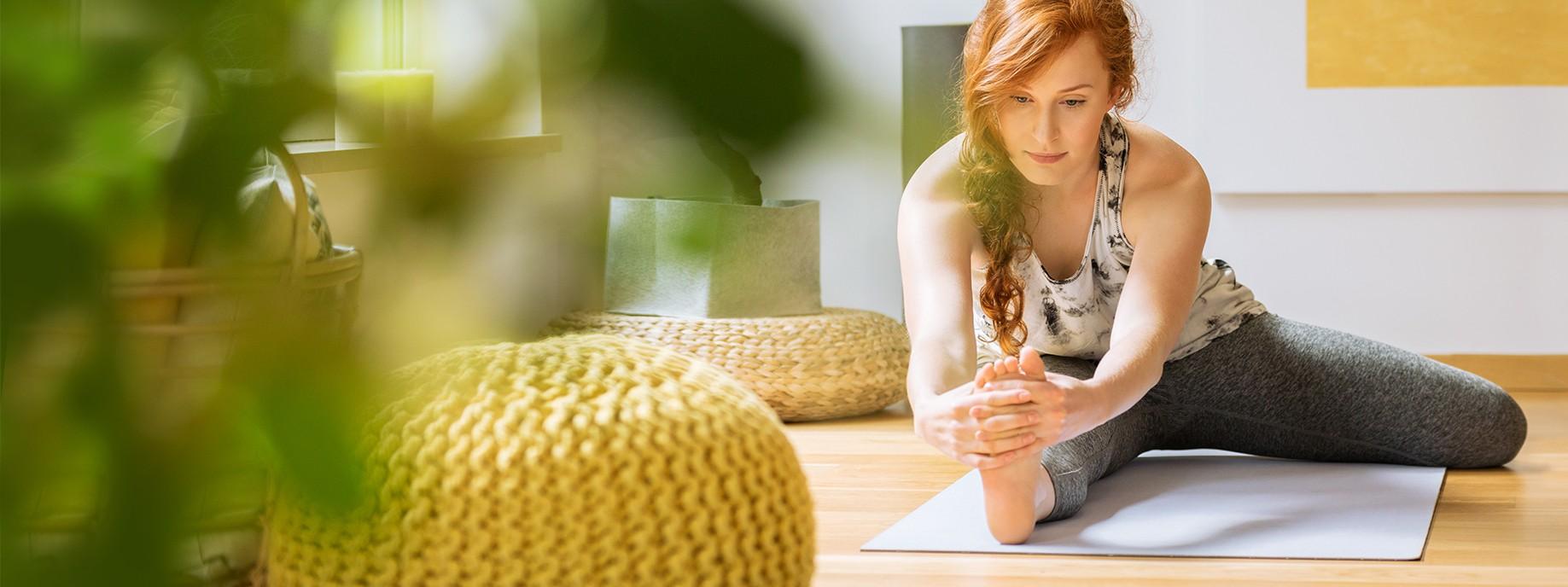 Eine junge Frau mit roten Haaren macht zu hause Dehnübungen