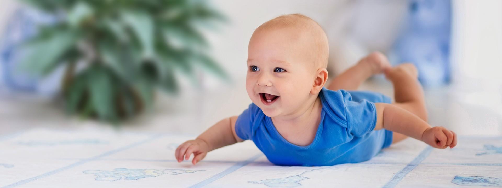 Baby im blauen Strampelanzug liegt auf dem Bauch, auf einer hellblauen Babydecke.