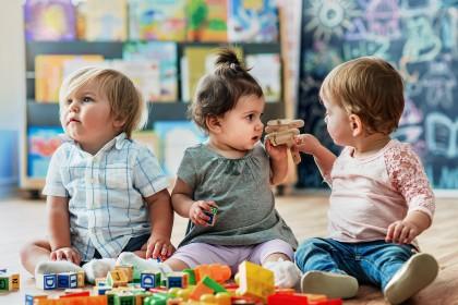 Drei kleine Kinder spielen mit einem Holzflugzeug und Holzbausteinen.