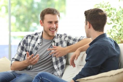 Zwei etwa 25 jährige Männer sitzen auf einem Sofa und unterhalten sich angeregt.