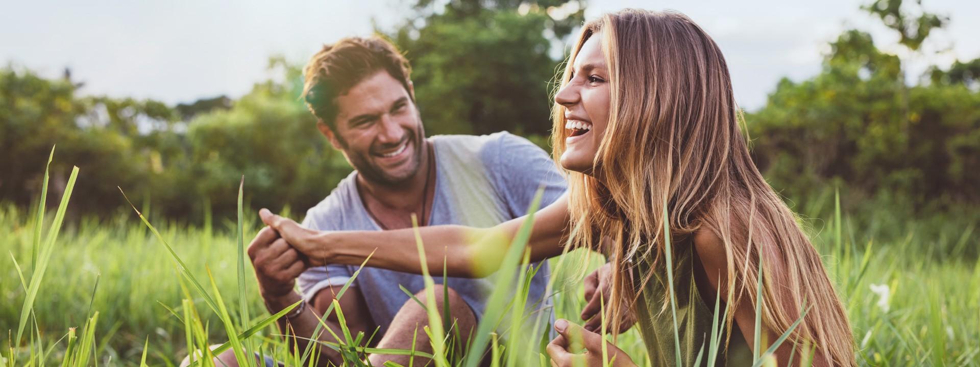 Ein junges Paar hält sich auf einer Wiese sitzend lachend an der Hand.