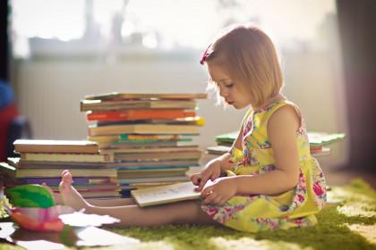 Ein etwa 4 jähriges Mädchen sitzt auf dem Boden in seinem Zimmer und schaut sich ein Buch an. Neben ihr steht ein großer Stapel von weiteren Büchern.