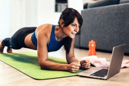 Frau macht Planks auf Fußboden vor einem Laptop