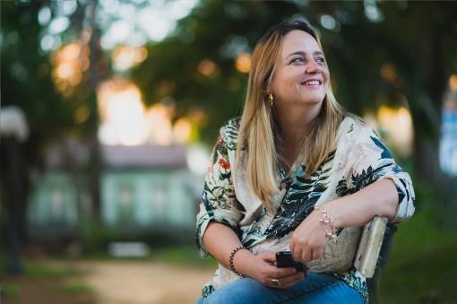 junge Frau sitzt zufrieden auf einer Bank