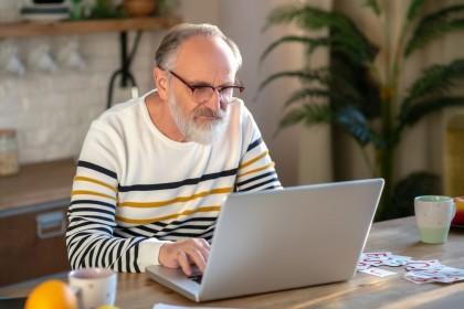 Älterer Mann sitzt an einem Laptop